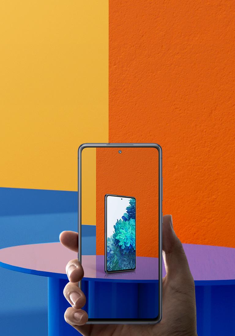 Рука, що тримає Galaxy S20 FE із зображенням з елементами доповненої реальності на екрані.